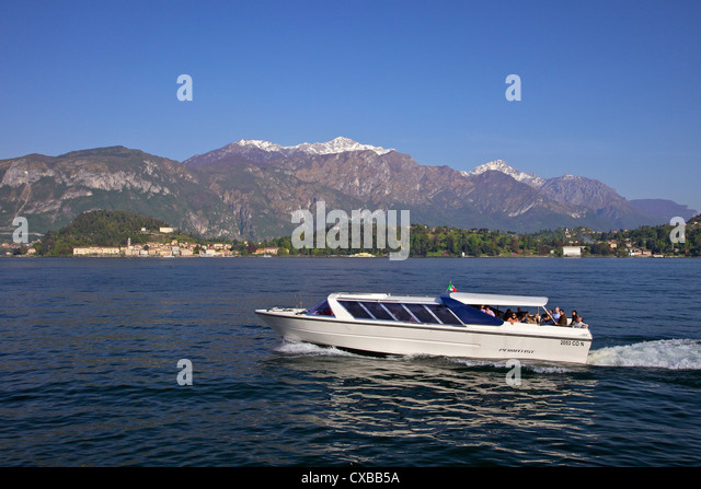 Pleasure boat crossing Lake Como from Bellagio in spring sunshine, Lombardy, Italian Lakes, Italy, Europe - Stock Image
