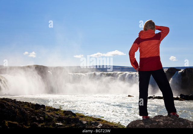 A woman hiker of explorer shot in golden evening light in front of a huge waterfall. On location at Godafoss waterfall, - Stock Image