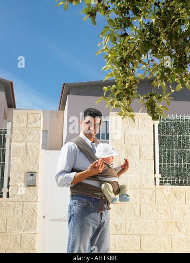 Father looking at camera with 5 month old baby in sling, urban location, Alicante, Spain, - Stock Image