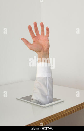 A man's hand gets out of a white tablet - Stock Image