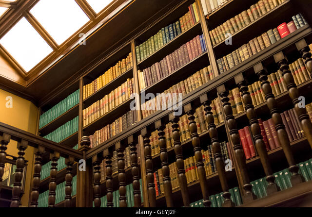Low angle view of Books arranged in bookshelves - Stock Image