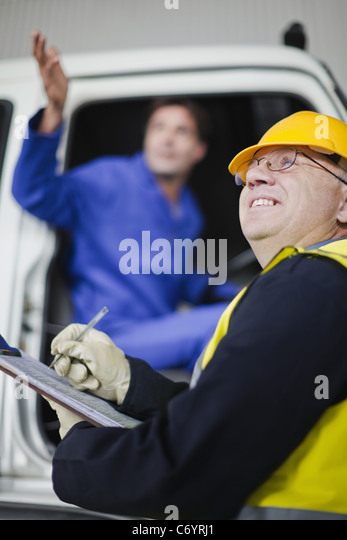 Truck driver talking to worker - Stock Image