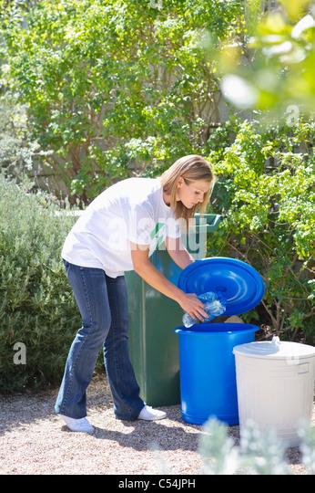 Woman throwing water bottles in garbage bin - Stock Image