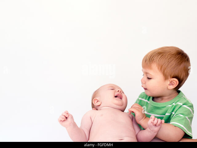 Young boy holding baby sister in arms - Stock Image
