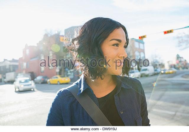 Woman looking away on city street - Stock Image