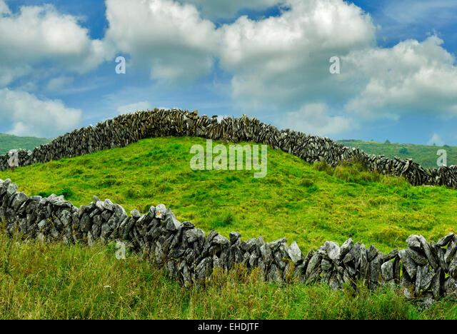Rock fence and clouds in The Burren. Ireland. - Stock-Bilder