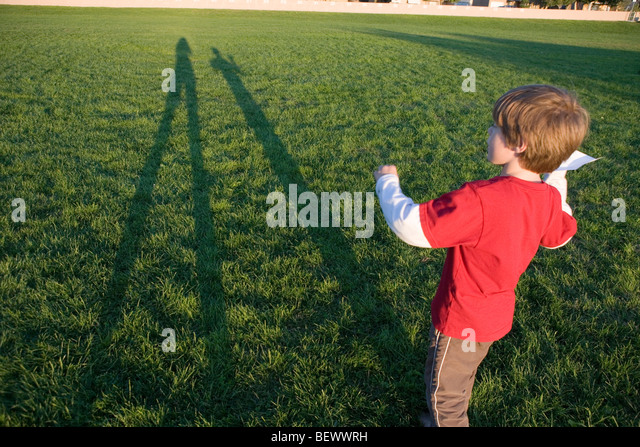 seven year old boy preparing to throw a paper airplane in an open field - Stock Image