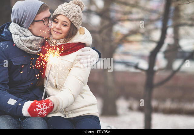 Amorous guy kissing his girlfriend in urban environment in winter - Stock Image