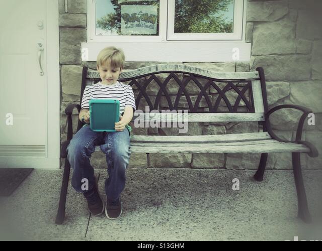 A young Pokémon fan on a bench checks his Pokédex outside a home. - Stock Image
