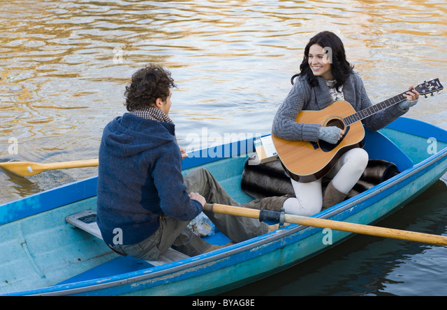 Girl playing guitar in row boat - Stock Image