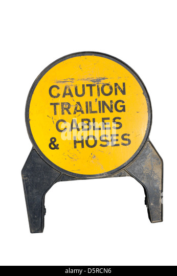 A sign warns of trailing cables and hoses in a dangerous working environment. - Stock Image
