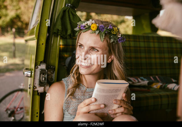 Hippie woman looking up from a book in van - Stock Image