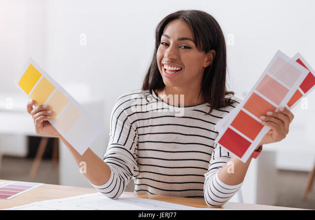 Happy positive woman holding colored pieces of paper - Stock Image