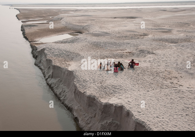 Villagers stopping to eat near the fragile edge of a sandspit in the River Ganges, Sonepur, Bihar, India, Asia - Stock Image
