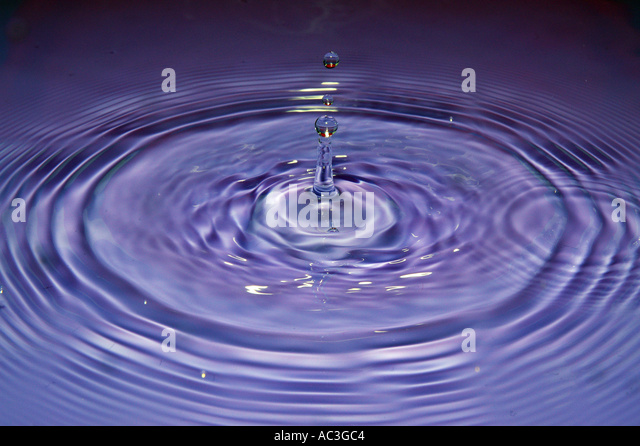 Water drop impact frozen mid splash with ripples and droplets - Stock Image