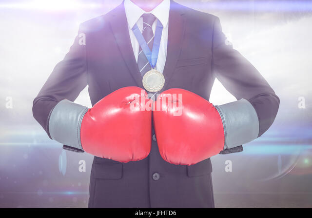 Businessman with boxing gloves against american football arena - Stock Image