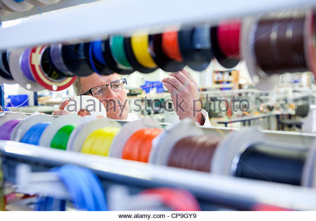 Engineer inspecting vibrant wire spools in laboratory - Stock Image