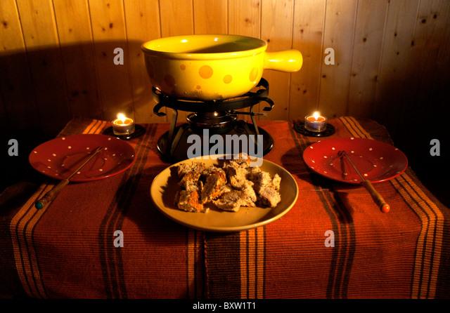 Käsefondue Caquelon on small table - Stock-Bilder