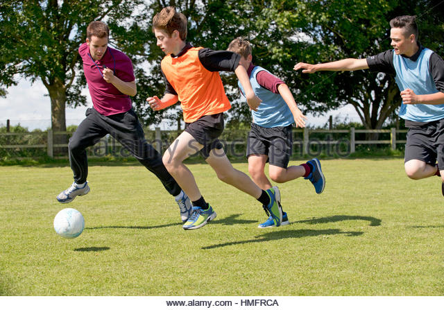 Middle schoolboys and teacher running playing soccer on field in physical education - Stock-Bilder