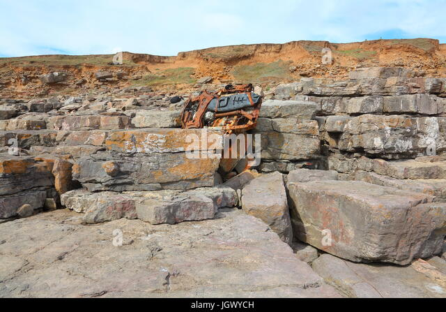 Looking upwards to the clifftop with the wreckage of a Beach Buggy firmly wedged into a crevice in the rocks on - Stock Image
