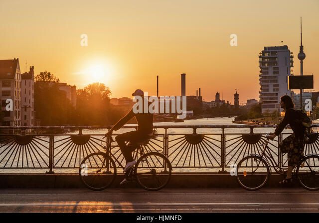 Oberbaumbruecke, Oberbaum bridge, pedestriants, bicycles, sunset, Alex, river Spree, Berlin - Stock Image