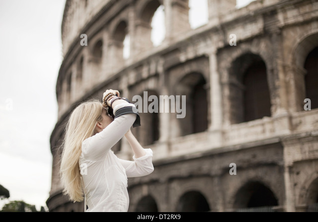 A woman outside the Colosseum amphitheatre in Rome taking photographs - Stock Image