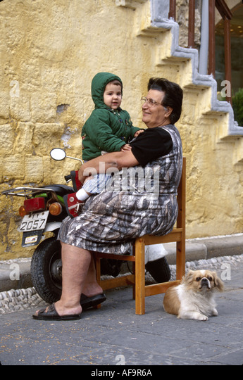 Greece Isle of Rhodes Old Town Jewish Martyrs Quarter medieval district residents grandmother child - Stock Image