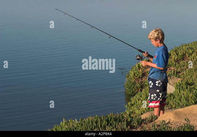 A young boy waits patiently for a fish to bite. - Stock Image