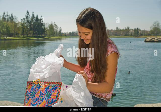 Mexican heritage. Hispanic/Caucasian girl opens gift.  MR  © Myrleen Pearson - Stock-Bilder