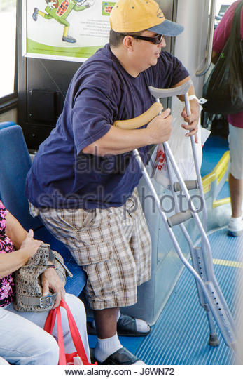 Miami Beach Florida Metrobus South Beach Local bus transportation crutches man disabled rider passenger gets up - Stock Image