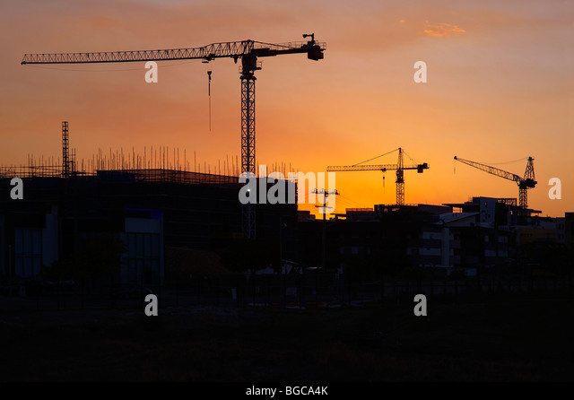 Tower cranes silhouetted on a construction site - Stock-Bilder