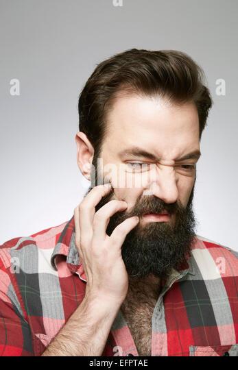 Studio portrait of young man scratching overgrown beard - Stock-Bilder