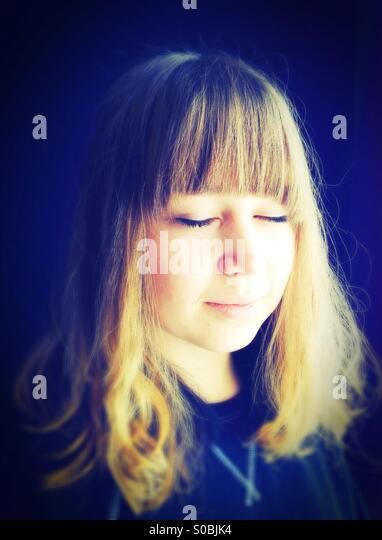 A teenage girl with her eyes closed, smiling slightly. - Stock Image