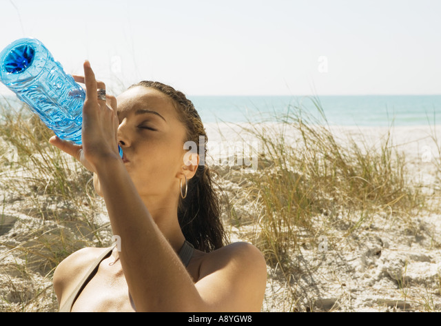 Woman drinking bottled water on beach - Stock Image