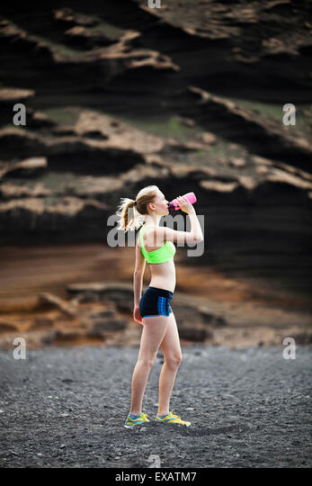 woman drinking water, running, jogging - Stock Image
