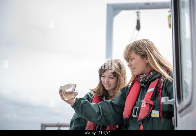 Female scientists inspecting sample of plankton on research ship - Stock Image