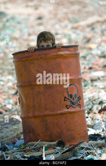 Child peeking over edge of metal barrel marked with skull and bones, surrounded by landfill - Stock Image