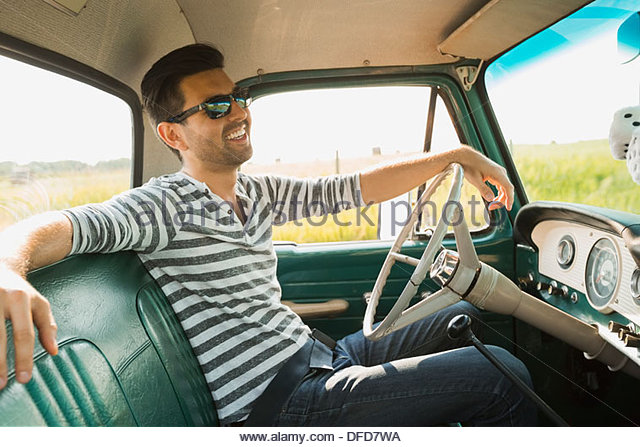 Man sitting in pick-up truck - Stock Image