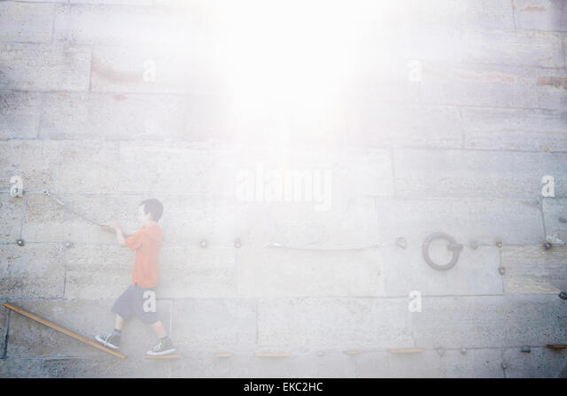Boy climbing along wall - Stock Image