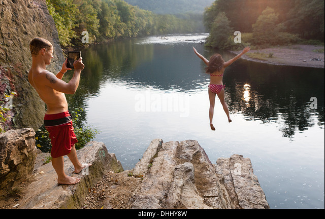 Young couple photographing jump from rock ledge, Hamburg, Pennsylvania, USA - Stock-Bilder