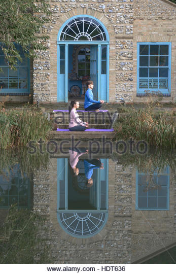 Young couple doing yoga on porch of stone building. - Stock Image