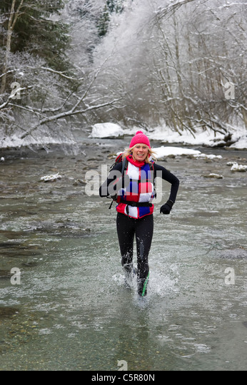 A runner ignores the cold water and enjoys a snowy river bed crossing. - Stock-Bilder