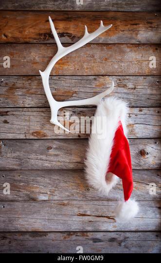 Red santa hat hanging from white reindeer antler - Stock Image