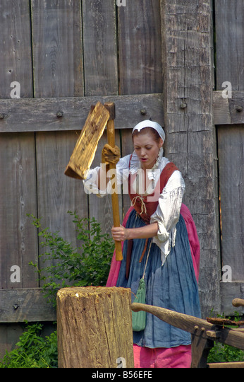Jamestown Settlement Virginia woman chopping wood blur action colonial dress costume - Stock Image