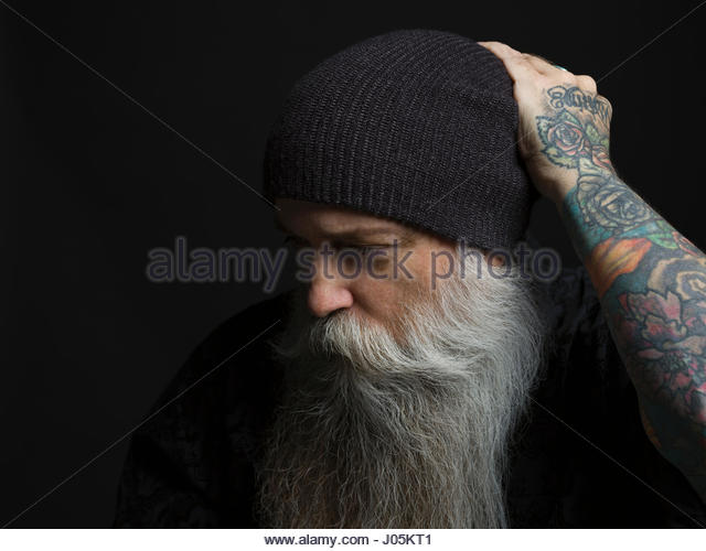 Portrait tattooed hipster man with gray beard and stocking cap against black background - Stock Image