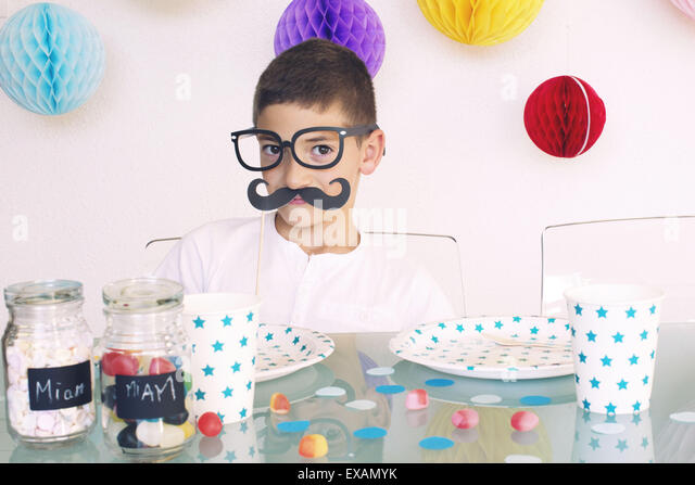 Boy wearing fake glasses and mustache at a birthday party - Stock Image