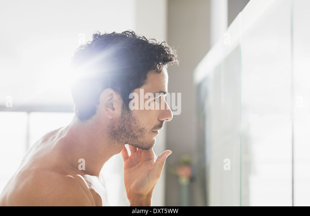 Man checking beard in bathroom mirror - Stock Image