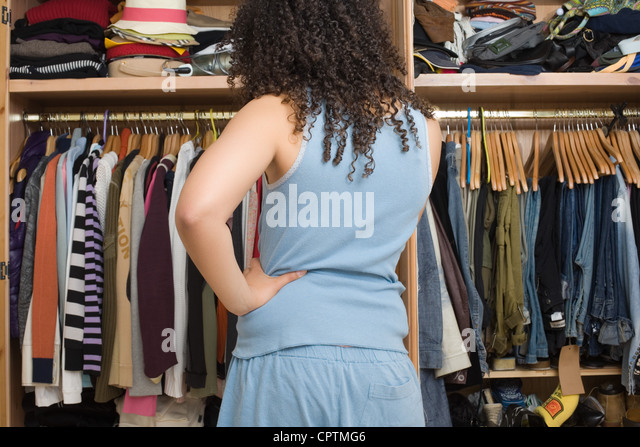 Woman in pajamas standing in front of open wardrobe - Stock Image