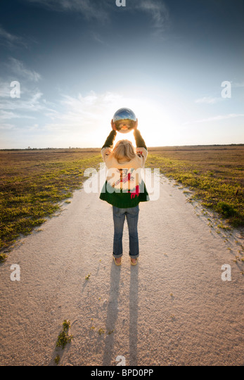 Rear view of woman standing on dirt road holding globe in air - Stock Image