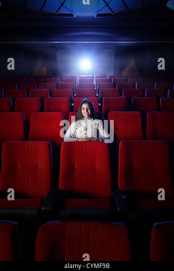 beautiful young woman alone sitting in a empty movie theater - Stock Image